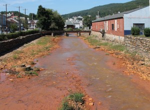 Orange-tinted Shamokin Creek, Pennsylvania.  Upstream mining acidified the water, causing dissolved iron to coalesce and coat the rocks and stream bottom.  Photo   Jake C 2014.